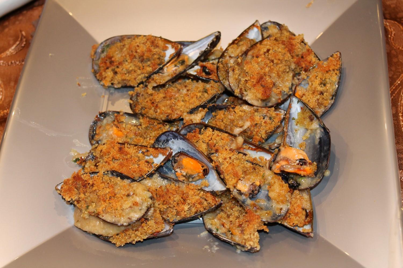 Cozze gratinate servite un piatto di colorazione grigio metallica