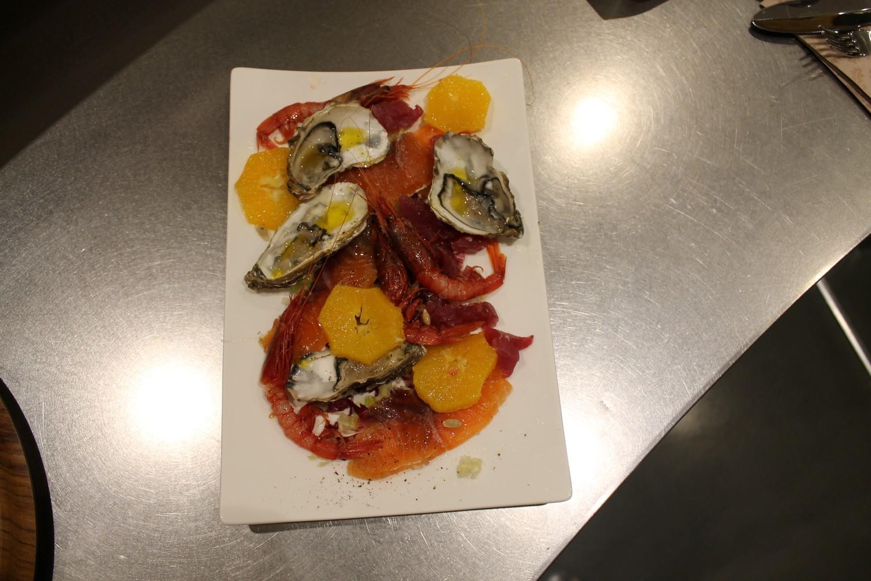 Composizione mediterranea di gamberi, ostriche, salmone e arance su piatto bianco