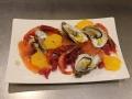 Gamberi, ostriche, salmone e arancia in composizione artistica su piatto bianco