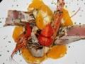Impiattamento di carni bianche poco cotte con gamberi, pomodorini e arance